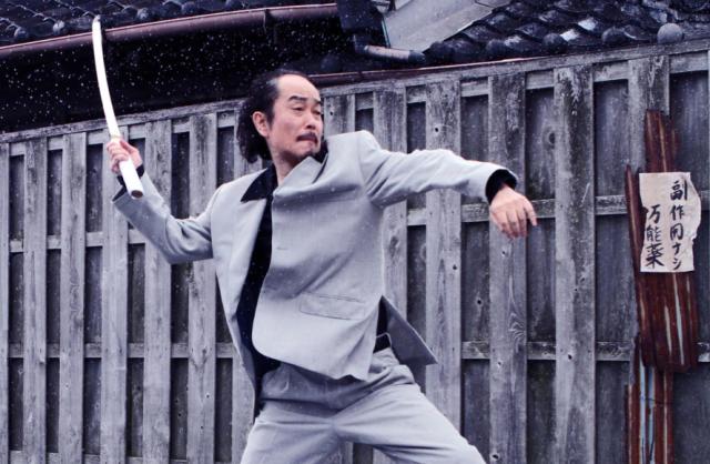 Lily Franky as Kamiura in Yakuza Apocalypse